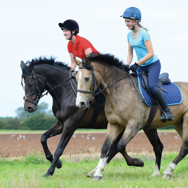 lady and girl cantering across the countryside